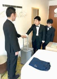 ホテルスタッフとして、客室まで荷物を運ぶ子どもたち