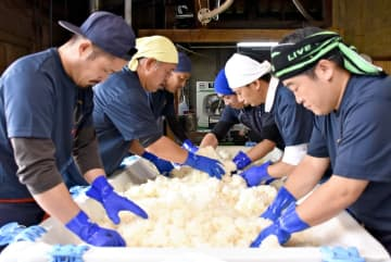 仕事の合間を縫って集まった多久未来プロジェクトのメンバー。蒸した米を手で丁寧にほぐした=多久市東多久町の東鶴酒造