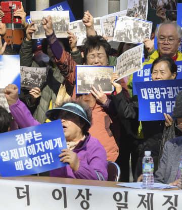 30日、ソウルの日本大使館前に集まり、元徴用工らの被害救済を求める「アジア太平洋戦争犠牲者韓国遺族会」のメンバーら(共同)