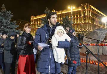 29日、モスクワ中心部のロシア連邦保安局(奥)の前で、赤ちゃんを抱き粛清犠牲者の名前を読み上げる男性ら(共同)