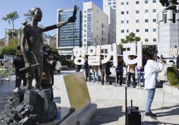 元徴用工像(左)が置かれた公園で「抗日通り」の看板(中央)を設置しようとする市民団体=30日、韓国・釜山(共同)