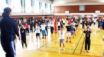 東海大体操部の学生に合わせて準備体操をする参加者