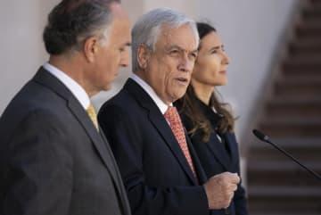 30日、チリで予定されていたAPEC首脳会議とCOP25の開催断念を発表するピニェラ大統領(中央)=首都サンティアゴ(チリ大統領府提供・AP=共同)