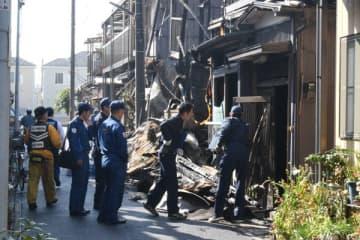 燃えた住宅を調べる警察官ら=30日午前10時半ごろ、川口市安行領根岸