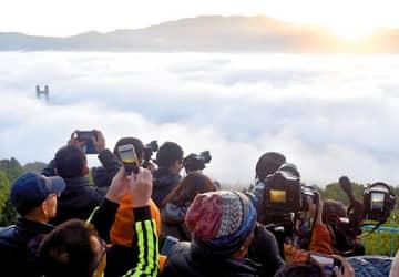 秩父市中心部を覆った雲海と日の出を撮影する見物客。中央左は秩父公園橋の一部=30日午前6時20分ごろ、秩父ミューズパーク展望台