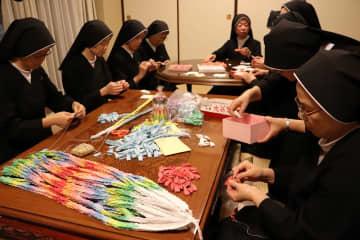 祈りのこもった一羽一羽をつなげていくシスターたち=出津修道院