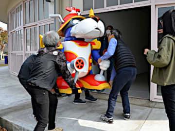 大型展示物を慎重に館内に運び込むスタッフら=30日、倉吉市鍛冶町1丁目の円形劇場くらよしフィギュアミュージアム