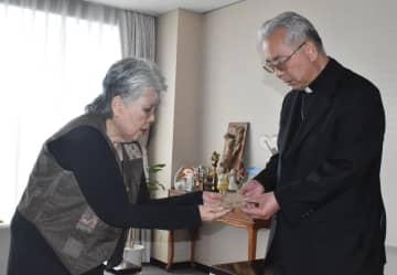 高見大司教(右)に被爆瓦を見せる竹下さん=長崎市、カトリック長崎大司教館