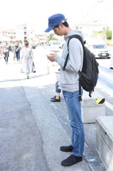 首里城から煙が上がる中、龍潭のほとりでツイッター投稿をする「レンタルなんもしない人」こと森本祥司さん=31日午前10時半前、那覇市