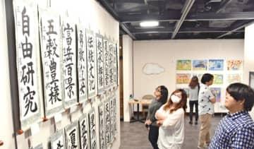 全琉図画・作文・書道コンクールの最優秀作品展が始まり、力作に見入る来場者=30日、那覇市のタイムスギャラリー