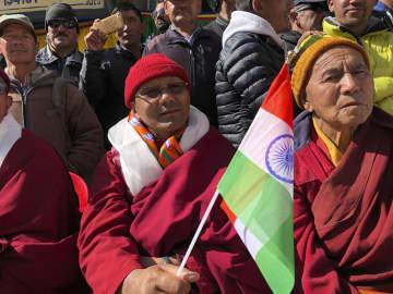 31日、インド北部の旧ジャム・カシミール州レーで、連邦直轄地となり国旗を掲げて祝福する男性ら(AP=共同)