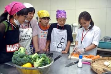 調理を通してベトナム人参加者(右)と交流を深める子どもら=大崎町中央公民館