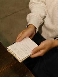 取材に応じる元臨時講師の男性。メモ帳には当時受けた嫌がらせ行為などが記されていた=姫路市内