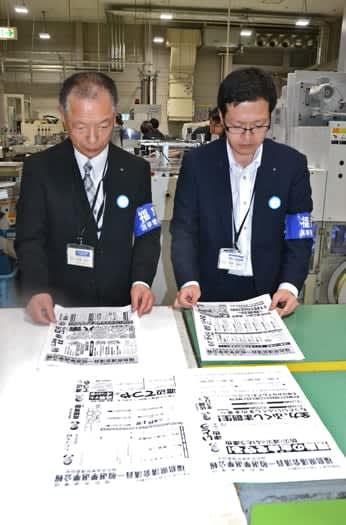 刷り上がった選挙公報を確認する県選管委の担当者=日進堂印刷所