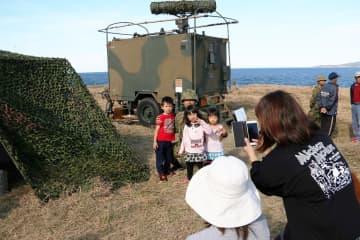 自衛隊の装備品を前に隊員と記念撮影する来場者=小値賀町