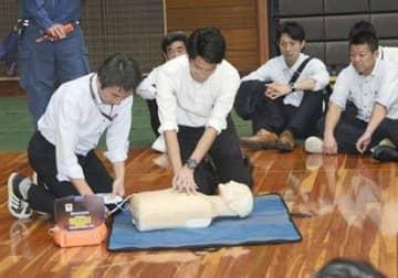 防災訓練でAEDを体験する大会関係者ら=熊本市西区