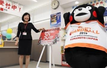 熊本水前寺公園郵便局の北岡千穂局長とともに、局内に設置したカウントダウンボードの日付を「30日」と表示して喜ぶくまモン=31日、熊本市中央区