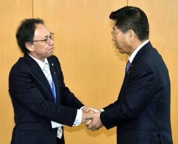 衛藤沖縄北方相(右)と握手する沖縄県の玉城デニー知事=1日午前、内閣府