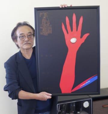 三重県伊勢市の市展で展示が不許可となった作品「私は誰ですか」を手にする制作者の花井利彦さん=10月31日、伊勢市