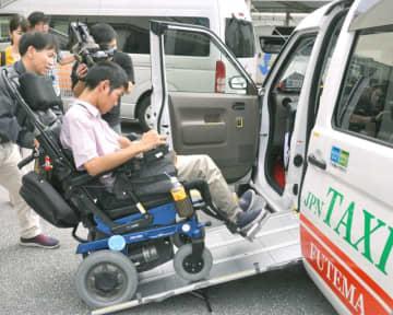 運転手に誘導されながらUDタクシーに乗り込む平良和希さん=30日、宜野湾市の県自立生活センター・イルカ