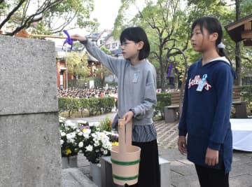 「あの子らの碑」に献水する児童=長崎市立山里小