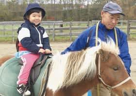 馬の背に乗り笑顔を見せる年中児