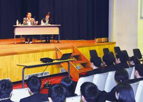 カンボジアでの教育機会向上を海星学院高校の生徒に説明するバンタイさん(壇上左)