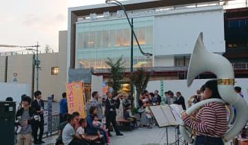 建設が進む諫早駅を前にジャズを演奏する大学生。通り掛かりの市民が耳を傾けた=諫早市永昌東町