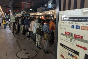 夜間でも列ができる四条河原町の京都市バス停留所(26日、下京区四条河原町)