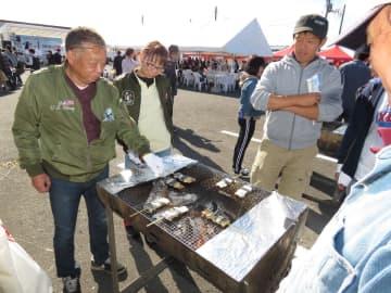 炭火であぶるサバの串焼きを楽しむ鯖サミット」来場者=2日、八食センター南側駐車場特設会場