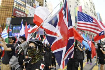 香港中心部で、世界各国の国旗を掲げながら各国の国歌を歌う若者ら=2日(共同)