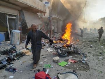 爆発が起きたシリア北部テルアビヤドの現場付近を歩く人=2日(ゲッティ=共同)