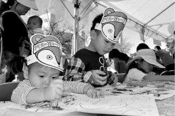 タヌキの塗り絵を楽しむ来場者=徳島市の藍場浜公園