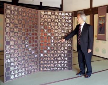 半世紀にわたり手掛けてきた精緻な刺繍作品を紹介する長艸さん(京都市上京区・妙顕寺)