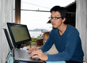 瀬戸内海を見渡せる自宅の縁側にパソコンを置いて仕事に励む菅原さん