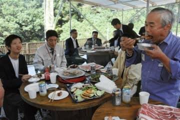 猪王のオープニングイベントのバーベキューでジビエを楽しむ参加者ら=八代市