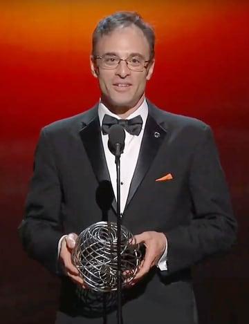 「ブレークスルー賞」の授賞式でトロフィーを手にあいさつする、ブラックホールの輪郭撮影に成功した国際研究チームの代表シェパード・ドールマン氏=3日、米カリフォルニア州(ユーチューブから)