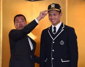 仮契約を終え、阪神の山本宣史スカウトに帽子をかぶせてもらう西純矢(右)=岡山市内