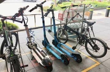 5日から歩道での走行が禁止される電動キックスケーター(中央3台)=4日、シンガポール中心部(NNA撮影)
