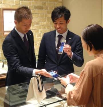 シャレオの店舗で、スマホを使ってサンフレッチェコインをためる森崎浩司さん(左)と和幸さん(中)