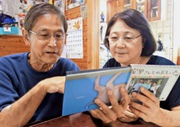 琉球大学医学部付属病院の看護師らから贈られたアルバムをめくりながら、闘病を振り返る安里猛さん(左)と妻の美佐子さん=宜野湾市内の自宅