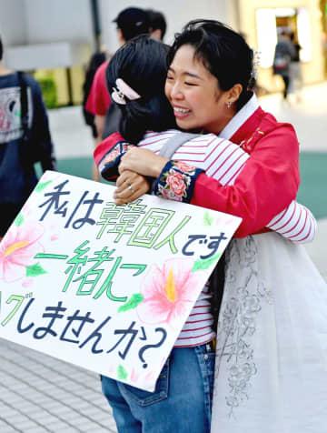 道行く人に日韓友好を呼び掛け、抱擁するユン・スヨンさん(右)=4日、那覇市・パレットくもじ前(田嶋正雄撮影)