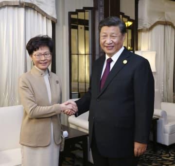 中国の習近平国家主席(右)と握手する香港政府トップの林鄭月娥行政長官=4日、上海(新華社=共同)