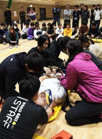 「スクープストレッチャー」という縦に分割できる担架を使い、負傷者を運ぶ訓練を受けるボランティアら=熊本保健科学大