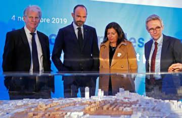 4日、2024年パリ五輪・パラリンピックの選手村の建築模型を見るフランスのフィリップ首相(左から2人目)=パリ郊外サントゥアンシュルセーヌ(ロイター=共同)