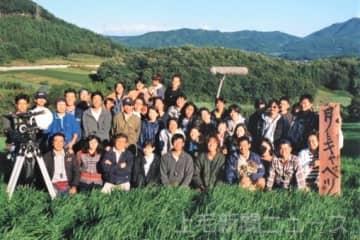 「月とキャベツ」の作品世界を象徴する草原で撮影された集合写真。前列中央が篠原監督、右隣が山崎さん=1996年9月、高山村