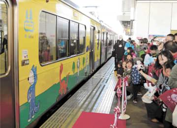 11ぴきのねこが描かれた列車をホームで出迎える家族連れ=青い森鉄道八戸駅