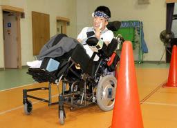 「筋電位車いす」に乗る練習をする構井遼さん。コーンをよけながら左右に操る=和田山特別支援学校