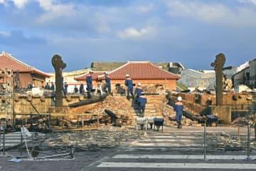 全焼した正殿で実況見分する消防職員と焼け残った龍柱2体=2日、那覇市首里当蔵町・首里城内