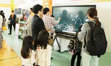 企業の紹介ブースで電子黒板の機能を学ぶ親子連れ